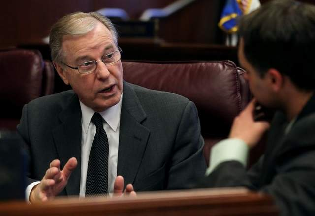 Nevada Sen. David Parks talks with intern Matthew Slagle on the Senate floor on Wednesday. Photo by AP/Cathleen Allison