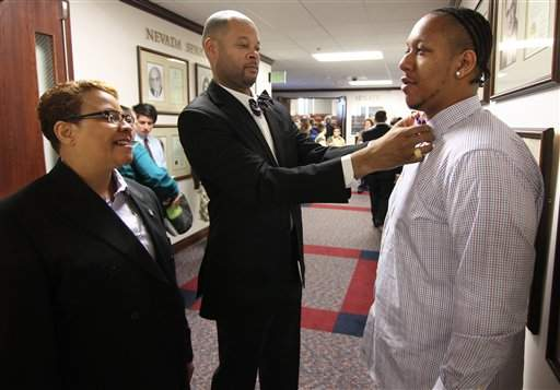 Nevada Sen. Patricia Spearman D-North Las Vegas, left, watches as Sen. Aaron Ford, D-Las Vegas fixes Spearman's nephew Andrew Davis' tie before opening day of the 77th Legislative Session in Carson City, Nev. on Monday, Feb. 4, 2013. / AP file Photo/Cathleen Allison)