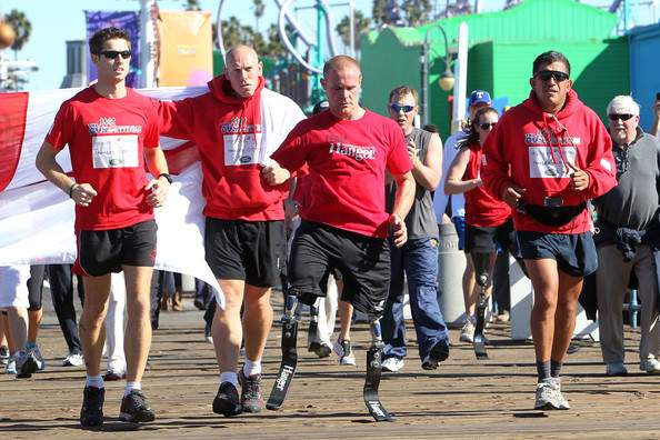 Above, Charles Padilla, right, British Royal Marine Mark Ormrod, front, and their team finish the Gumpathon, a run across America, on the Santa Monica pier. / Photo provided by Charles Padilla