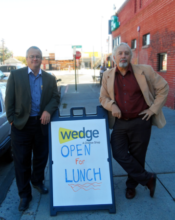 "Caption: Steve Funk and Randy Pease stand by the Wedge- A Cheeseshop sign on the day they were  chosen to be ""Ca$h Mobbed."""